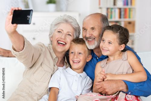 großeltern fotografieren die familie mit handy - 55768438