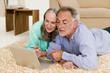Älteres Ehepaar in Wohnzimmer, auf dem Boden liegend mit Laptop
