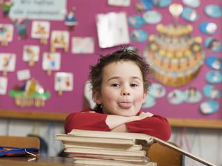 Junge sitzt in der Schule, stützt sich auf Stapel Bücher