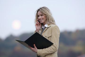 Geschäftsfrau mit Handy, hält Dokumente