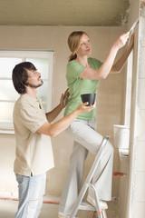 Junges Paar auf Baustelle, Frau mit einem Spachtel, Seitenansicht