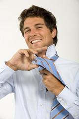 Junger Mann bindet Krawatte, Portrait
