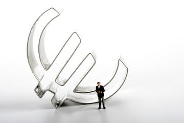 Geschäftsmann-Figur vor Euro-Symbol