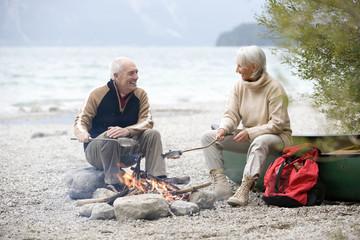 Deutschland, Bayern, Walchensee, Älteres Paar sitzt am Lagerfeuer und grillt