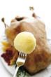 Kartoffelknödel auf Gabel, Gänsebraten im Hintergrund