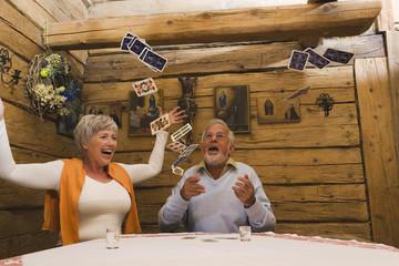 älteres Paar wirft Spielkarten in die Luft