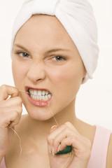 Nahaufnahme von einer jungen Frau, mit Zahnseide