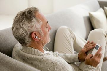 Erwachsener hört Musik mit MP3-Player, Nahaufnahme