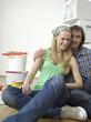 Junges Paar sitzt auf Boden, Blick zur Kamera