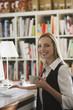 Junge Frau im Büro mit Kaffeetasse, lächelnd, Porträt