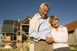 Älteres Paar vor noch nicht fertiggestelltem Haus