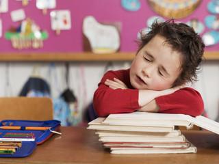 Junge sitzt am Schreibtisch und stützt sich auf Stapel Bücher, die Augen geschlossen