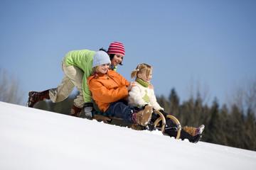 Drei Kinder auf Schlitten