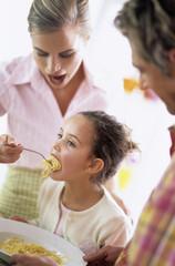 Mutter füttert Tochter mit Spaghetti
