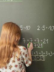 Mädchen an der Tafel in der Schule, Rechenaufgabe lösend
