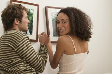Junges Paar hängt Bilderrahmen auf