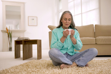 Ältere Frau mit Tasse Tee, die Augen geschlossen