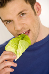 Junger Mann isst Salatblatt, Nahaufnahme
