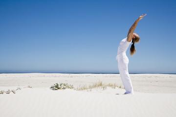 Frau bei Yogaübung am Strand