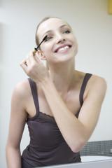Junge Frau benutzt Mascara, lächelnd, Porträt