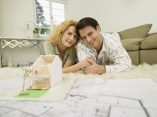 Junges Paar in Wohnzimmer, lächelnd, Porträt