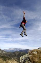 Mann springt über Abhang in den Bergen