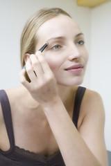 Junge Frau beim Augenbrauen zupfen, close up
