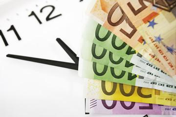 Euro-Banknoten und Uhr, Symbol für Zeit ist Geld