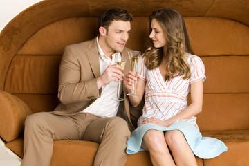 Junges Paar auf dem Sofa hält Champagner-Gläser, lächelnd