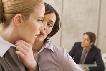 Geschäftsfrauen in einer Sitzung, flüstern