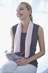 Junge Frau mit Flasche Wasser, Handtuch um den Hals, Portrait