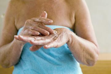 Ältere Frau im Handtuch eingewickelt, Eincremen der Hände, Nahaufnahme