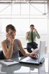 Teamwork, Frau mit Laptop während eines Telefonates