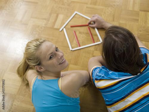 Paar auf dem Boden liegend, Gebäude Haus mit Stiften