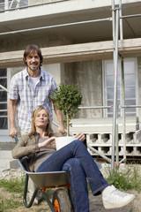 Junges Paar auf der Baustelle, Frau in der Schubkarre