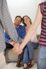 Teenager-Paar Händchen haltend, Eltern auf dem Sofa