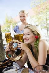 Deutschland, Bayern, Oberbayern, Junge Frau im Biergarten hält Brezel, Portrait