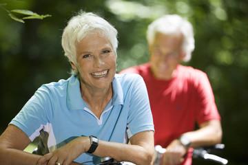 Älteres Paar mit Fahrrädern, Frau lächelnd, Porträt