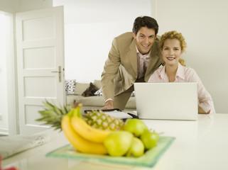 Junges Paar lächelnd mit Laptop