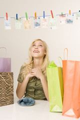 Blonde Frau trocknet Geld auf einer Wäscheleine, Portrait
