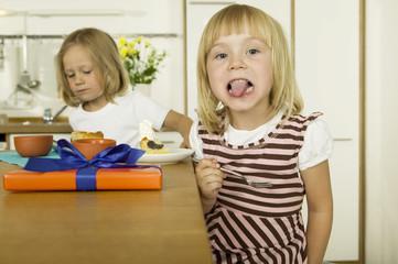 Zwei kleine Mädchen, Kuchen essen in der Küche