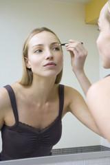 Junge Frau zupft ihre Augenbrauen