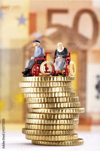 Figuren in Rollstühlen auf Stapel von Münzen