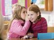 Mädchen flüstern im Klassenzimmer