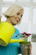 Ältere Frau gießt Zimmerpflanze, lächelnd