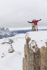 Italien, Südtirol, Paar in Winterkleidung auf Berggipfel, Jubel