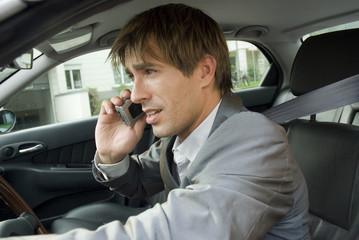 Geschäftsmann mit Handy im Auto, Seitenansicht, Nahaufnahme