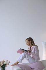 Junge Frau liest Zeitschrift, Seitenansicht