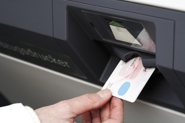 Hand schiebt Kreditkarte in Cash-Terminal, Nahaufnahme