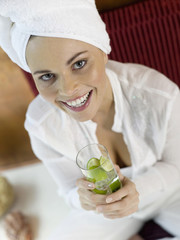 Frau sitzt auf einem Kissen mit einem Glas Limonenwasser, Nahaufnahme